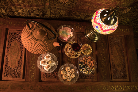 Arabian tea in glass with eastern snacks on vintage wooden surface. Eastern tea concept. Low light lounge interior with carpet. Empty space. View from top