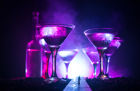 Abstract alcoholism concept. Silhouette of a man standing in the middle of the road on a misty night with giant glasses filled with alcoholic beverage. Creative artwork decoration