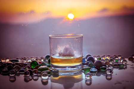 A Glass Of whiskey with ice and gold sunlight. Outdoor shot of whiskey with splash on sunset background. Selective focus