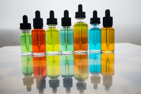 Vape concept. Beautiful colorful vape liquid glass bottles outdoor on chessboard. Useful as background or electronic cigarette advertisement. Selective focus