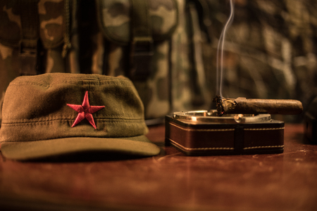 Close up of a Cuban cigar and ashtray on the wooden table. Communist dictator commander table in dark room. Army general`s work table concept. Artwork decoration 版權商用圖片