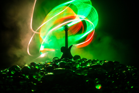 Music concept. Acoustic guitar on a dark background under beam of light with smoke. Emptry space for text. Fire effects. Surreal guitar Stock Photo