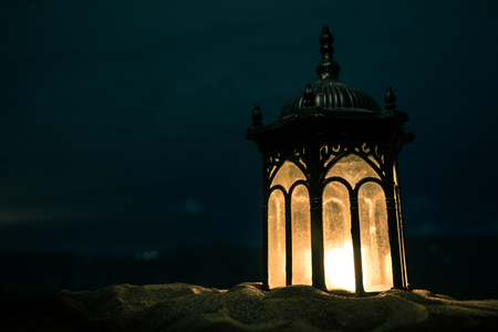 Ornamental Arabic lantern with burning candle glowing at night. Festive greeting card, invitation for Muslim holy month Ramadan Kareem. Stock Photo