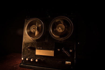 Old vintage reel to reel player and recorder on dark toned foggy background. Analog Stereo Open Reel Tape Deck Recorder Player with Reels. Selective focus