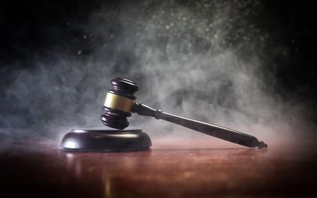 Tema de la ley, mazo del juez sobre un escritorio de madera con la estatua de Lady Justice. Martillo de ley sobre fondo oscuro brumoso con luz. Enfoque selectivo Foto de archivo