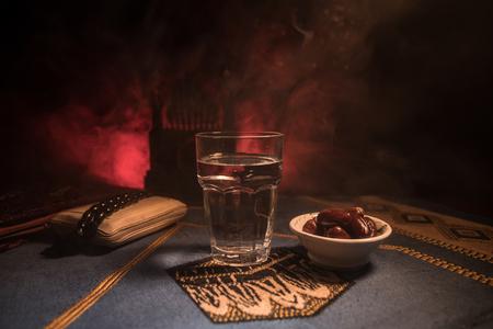 Agua y dátiles. Iftar es la cena. Vista de la decoración de vacaciones de Ramadán Kareem en alfombra. Tarjeta de felicitación festiva, invitación para el mes sagrado musulmán de Ramadán Kareem. Enfoque selectivo