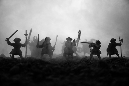 Battle scene. Military silhouettes fighting scene on war fog sky background. The musketeer soldiers Silhouettes below Cloudy Skyline at sunset. Artwork Decoration. Selective focus 스톡 콘텐츠