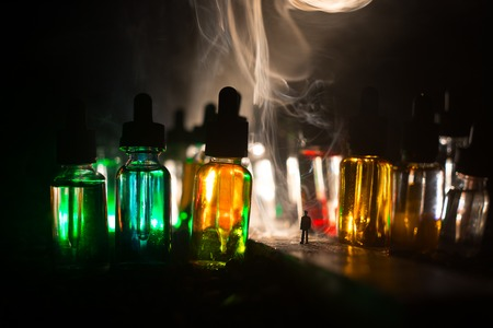 Vape concept. Silhouette of a man standing in the middle of the road on a misty night with giant glass bottles filled with electronic cigarette liquid. Colorful foggy clouds with light on background.