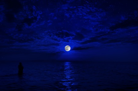 Colorful sky with cloud and bright full moon over seascape in the evening. Silhouette of a man at the sea