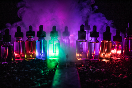 Vape concept. Silhouette of a man standing in the middle of the road on a misty night with giant glass bottles filled with electronic cigarette liquid. Colorful foggy clouds with light on background. Imagens