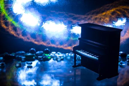 Concept créatif. Décoration d'œuvres d'art avec piano sur fond brumeux aux tons sombres avec lumière. Mise au point sélective Banque d'images