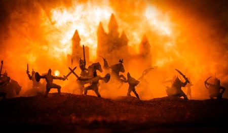 Escena de batalla medieval con caballería e infantería. Siluetas de figuras como objetos separados, lucha entre guerreros en el fondo de niebla al atardecer. Enfoque selectivo Foto de archivo