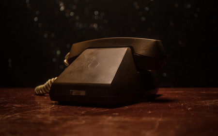 old black telephone on old wood plank with art dark background with fog and toned light. empty space. Selective focus