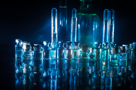 Pharmacy and chemistry theme. Test glass flask with solution in research laboratory. Science and medical background. Laboratory test tubes on dark toned background , science research equipment concept Imagens