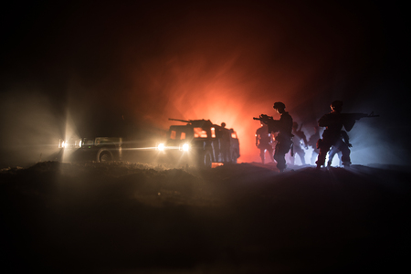 War Concept. Battle scene on war fog sky background, Fighting silhouettes Below Cloudy Skyline at night. Army vehicle with soldiers artwork decoration