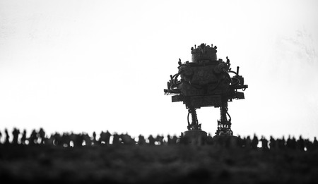 Artwork decoration. Silhouette of giant robot prepare attack crowd at sunset. Horror view of futuristic cyborg going to attack scared people. Selective focus.