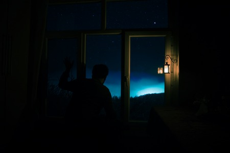 Silhouette of a man looking a dreamlike galaxy through a window. Fantasy picture with old vintage lantern at the window inside dark room. Stock Photo