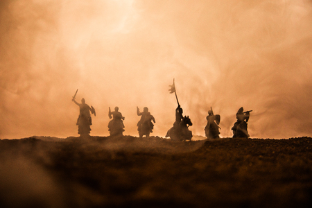 Medieval battle scene with cavalry and infantry. Silhouettes of figures as separate objects, fight between warriors on sunset foggy background. Selective focus Imagens