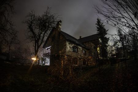 Vieille maison avec un fantôme dans la forêt la nuit ou Abandoned Haunted Horror House dans le brouillard. Ancien bâtiment mystique dans la forêt d'arbres morts. Arbres la nuit avec la lune. Lumières surréalistes. Concept d'Horreur Halloween