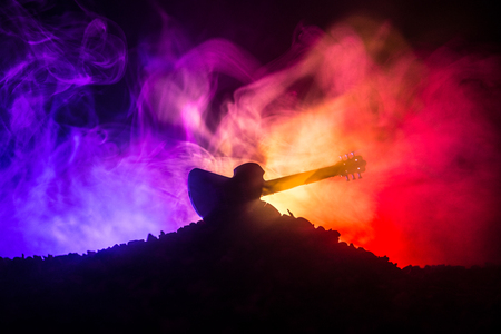 Music concept. Acoustic guitar on a dark background under beam of light with smoke. Emptry space for text. Fire effects. Surreal guitar 版權商用圖片