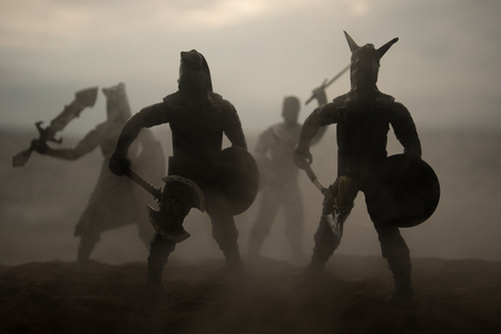 Medieval battle scene artwork decoration with toys. Silhouettes of figures as separate objects, fight between warriors on sunset foggy background. Selective focus Imagens
