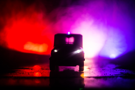 Police cars at night. Police car chasing a car at night with fog background. 911 Emergency response police car speeding to scene of crime. Selective focus Standard-Bild - 121516168