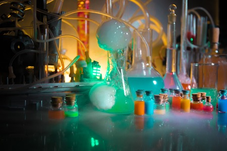 Pharmacy and chemistry theme. Test glass flask with solution in research laboratory. Science and medical background. Laboratory test tubes on dark toned background , science research equipment concept Stock Photo