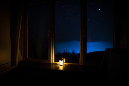 Nachtszene von Sternen durch das Fenster aus der Dunkelkammer gesehen. Nachthimmel im dunklen Raum mit Blick aus dem Fenster mit alter Vintage-Laterne. Langzeitbelichtung Standard-Bild