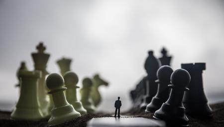Concept d'échecs d'idées d'entreprise et de stratégie. Silhouette d'un homme debout au milieu de la route avec des figures d'échecs géantes. Petit homme d'affaires sur la voie du succès ou des ennuis. Décoration d'œuvres d'art