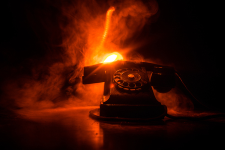 old black telephone on old wood plank with art dark background with fog and toned light. empty space. Selective focus Stock Photo