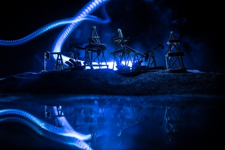 Artwork decoration. Oil pumps and oil rigs energy industrial machines for petroleum at night with fog and backlight. Energy industrial concept. Selective focus Imagens