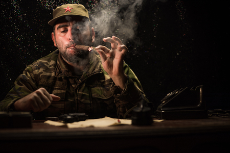 The evil dictator sitting on table. Angry communist general sitting at headquarter or Cuban commander in dark room. Studio decoration