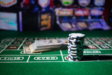 Cards and chips on green felt casino table. Abstract background with copy space. Gambling, poker, casino and cards games theme. Casino elements on green. Selective focus Reklamní fotografie