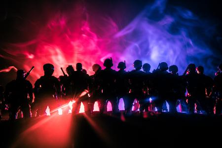 Anti-Bereitschaftspolizei gibt Signal, bereit zu sein. Regierungsmachtkonzept. Polizei in Aktion. Rauch auf einem dunklen Hintergrund mit Lichtern. Blaurot blinkende Sirenen. Diktaturmacht