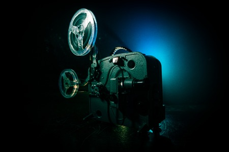 Old vintage movie projector on a dark background with fog and light. Concept of film-making. Selective focus