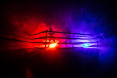 Hombre y mujer de boxeo en el ring. Concepto de deporte. Decoración de obras de arte con juguetes sobre fondo oscuro en tonos brumosos.