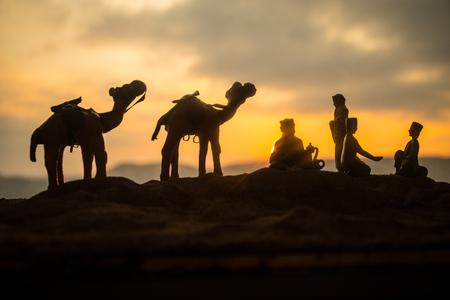 Camel caravan going through the sand dunes in the desert at sunset. Eastern travel concept. Artwork decoration