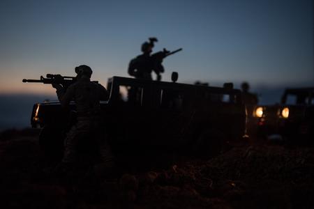 Kriegskonzept. Kampfszene auf Kriegsnebelhimmelhintergrund, Kampfschattenbilder unter bewölkter Skyline nachts. Armeefahrzeug mit Soldatenkunstdekoration