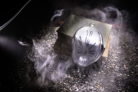 Concept de temps. Horloge de fusion douce déformée sur les vieux livres. Avec un fond brumeux aux tons sombres. Mise au point sélective Banque d'images