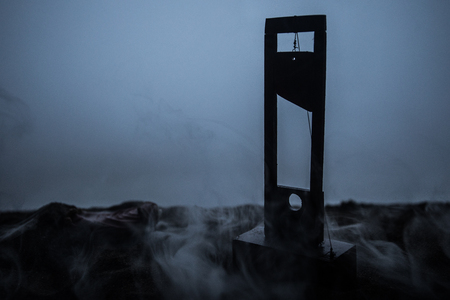Horror view of Guillotine. Close-up of a guillotine on a dark foggy background. Execution concept
