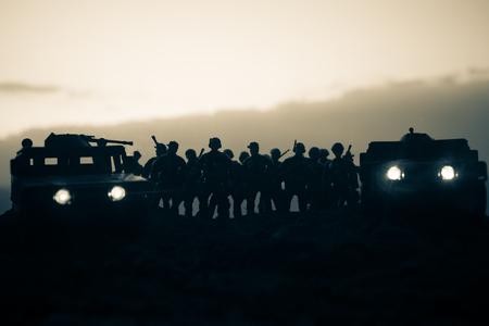 Auto di pattuglia militare sullo sfondo del tramonto. Concetto di guerra dell'esercito. Sagoma di veicolo blindato con soldati pronti ad attaccare. Decorazione di opere d'arte. Messa a fuoco selettiva