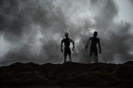 Horror Halloween concept. Silhouettes of scary zombies on misty field walking at the evening. Selective focus. Creative artwork decoration