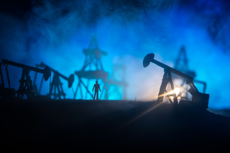 Engineering man standing against beautiful dusky sky of oil refinery plant. Silhouette of a man standing on the road at the oilfield. Scene use for energy of fossil fuel and industry topic background