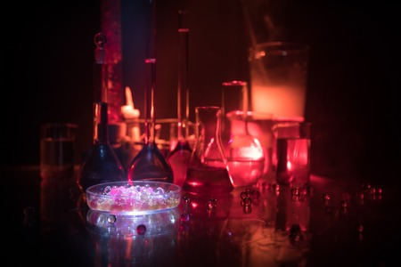 Pharmacy and chemistry theme. Test glass flask with solution in research laboratory. Science and medical background. Laboratory test tubes on dark toned background , science research equipment concept
