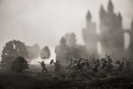Medieval battle scene with cavalry and infantry. Silhouettes of figures as separate objects, fight between warriors on sunset foggy background. Selective focus Stock fotó