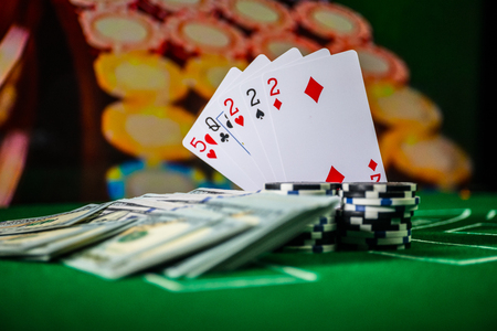 Cards and chips on green felt casino table. Abstract background with copy space. Gambling, poker, casino and cards games theme. Casino elements on green. Selective focus Imagens