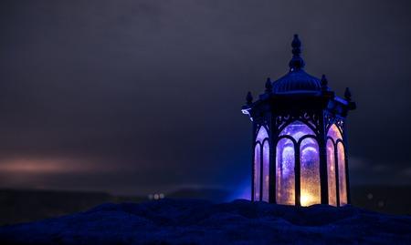 Ornamental Arabic lantern with burning candle glowing at night. Festive greeting card, invitation for Muslim holy month Ramadan Kareem. Фото со стока