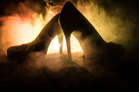 Artwork decoration. Silhouette of a man standing in the middle of the road on a misty night with giant high heel women shoes. Women power or women domination concept. Selective focus