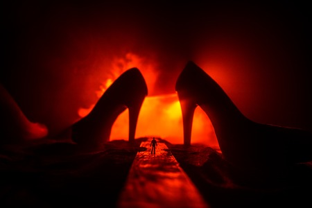 Artwork decoration. Silhouette of a man standing in the middle of the road on a misty night with giant high heel women shoes. Women power or women domination concept. Selective focus Banco de Imagens