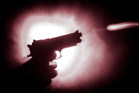 Mano maschio che tiene la pistola su sfondo nero con luci posteriori dai toni di fumo. Siluetta di una pistola in mano. Concetto di criminalità. Messa a fuoco selettiva